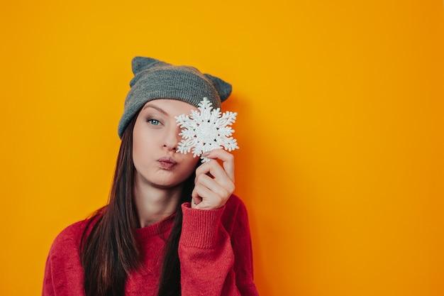 Kobieta w szarym kapeluszu na pomarańczowym tle. młoda kobieta w swetrze i kapeluszu trzyma płatek śniegu. kartka świąteczna z płatka śniegu.