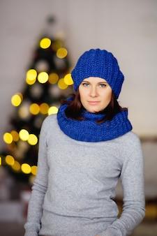 Kobieta w szarym swetrze i niebieskiej czapce i szaliku z dzianiny na tle świateł bokeh rozmytej choinki