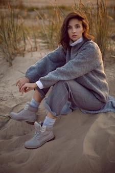 Kobieta w szarym swetrze i spodniach siedzi na plaży w butach o zachodzie słońca przy trawie
