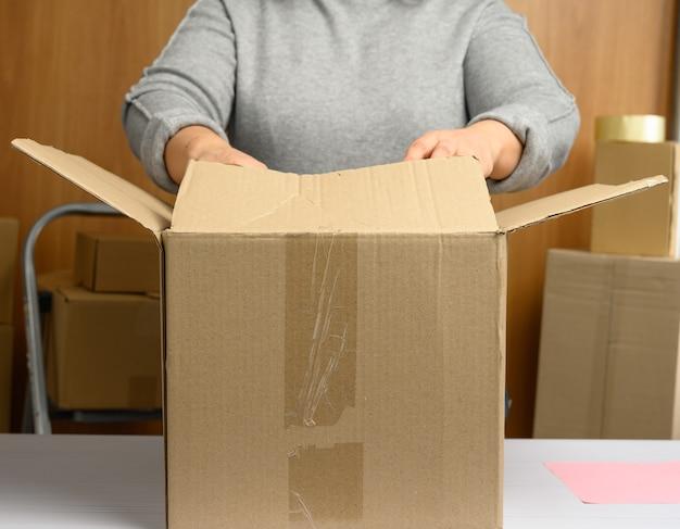 Kobieta w szarym swetrze pakuje brązowe kartony na białym stole, za stosem pudeł. ruchoma koncepcja