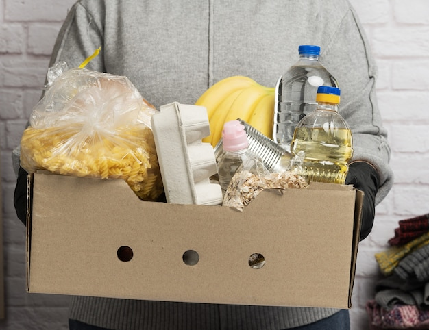 Kobieta w szarym swetrze pakuje jedzenie w karton, koncepcja pomocy i wolontariatu, darowizny
