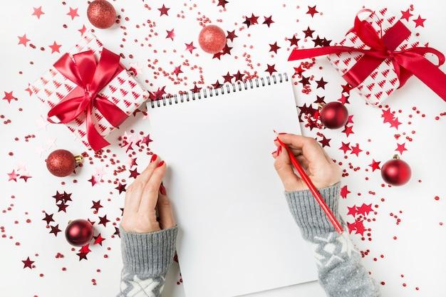 Kobieta w szarym swetrze pisze listę kontrolną planów i marzeń na przyszły rok. lista życzeń na boże narodzenie. lista rzeczy do zrobienia na nowy 2020 rok z czerwonym wystrojem świątecznym.