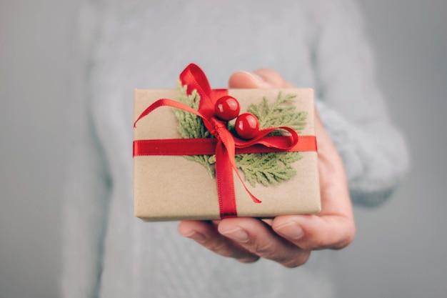 Kobieta w szarym swetrze trzyma mały świąteczny prezent.