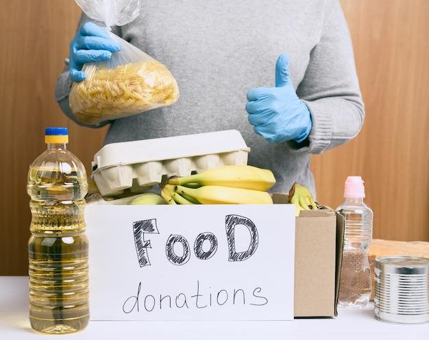 Kobieta w szarym swetrze wkłada do tekturowego pudełka różne potrawy, owoce, makarony, olej słonecznikowy w plastikowej butelce i przetwory. koncepcja darowizn i wolontariatu