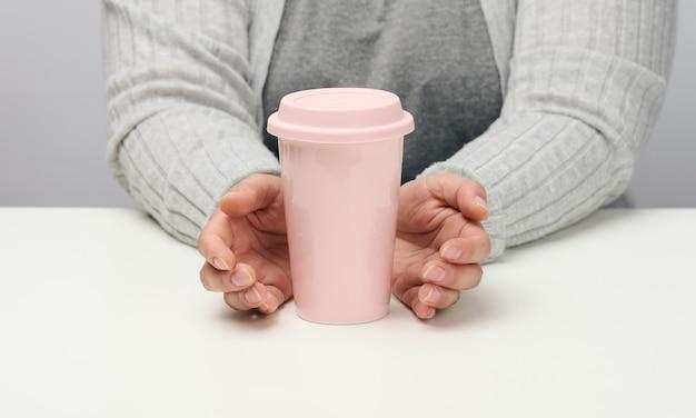 Kobieta w szarym ubraniu trzyma różowy ceramiczny kubek, kobieta siedzi przy białym stole, początek dnia, poranek