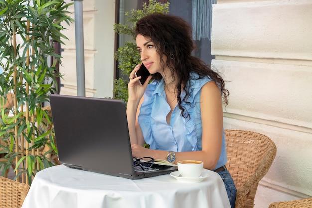Kobieta w szkle pracuje zdalnie z laptopem i telefonem w kawiarni. piękna brunetka używać notatnika w kawiarni. szczęśliwy bizneswoman dzwoni na telefonie komórkowym i bierze. wolny zawód