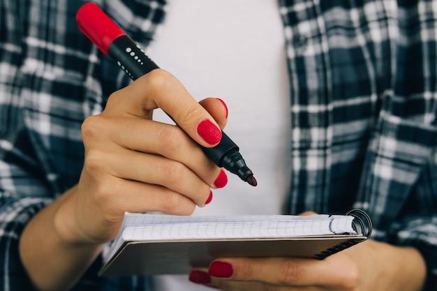 Kobieta w szkockiej kraty koszula i czerwonym manicure'u filc pióra writing w notatniku