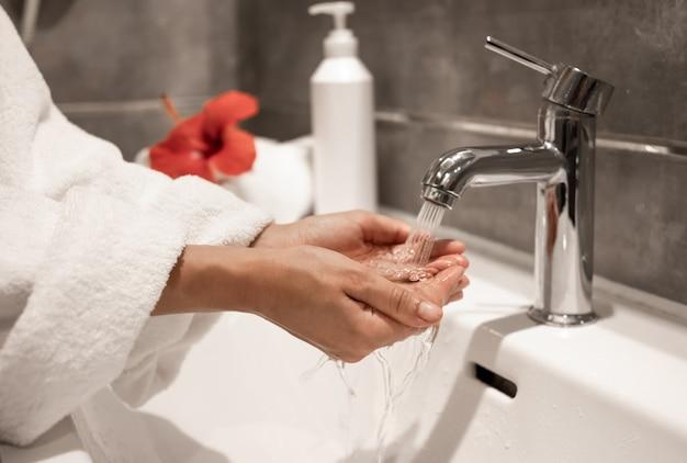 Kobieta w szlafroku myje ręce pod bieżącą wodą z kranu