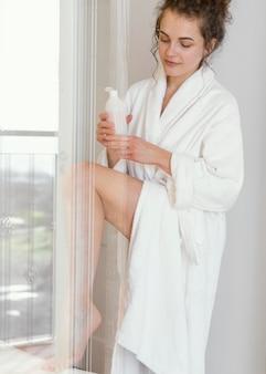 Kobieta w szlafroku stosując balsam