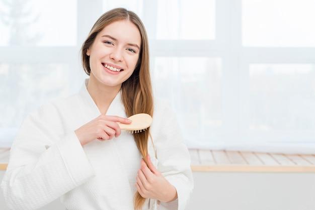 Kobieta w szlafroku szczotkuje włosy