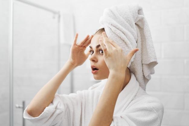 Kobieta w szlafroku w szlafroku przed lustrem patrzy na jej twarz