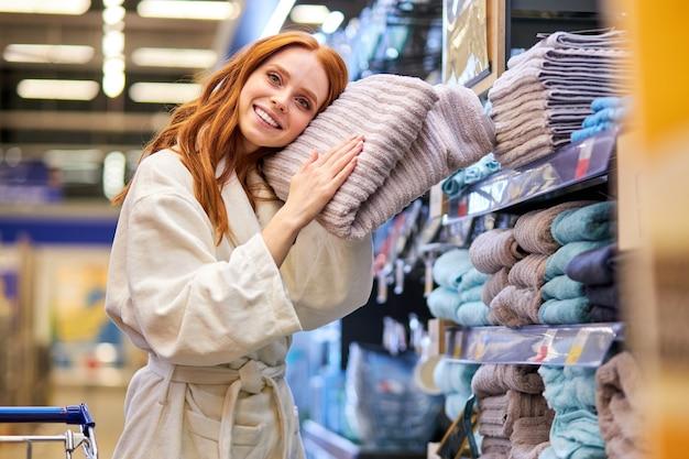 Kobieta w szlafroku wybiera w supermarkecie nowy ręcznik, kupuje, chce kupić, polubić. koncepcja czasu zakupów
