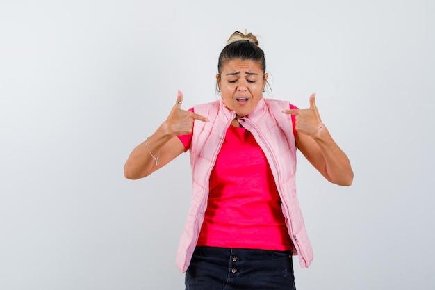 Kobieta w t-shircie, kamizelce, która wskazuje na siebie i wygląda na zaniepokojoną