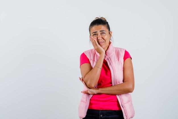 Kobieta w t-shircie, kamizelce opierając policzek na dłoni i wyglądająca na smutną