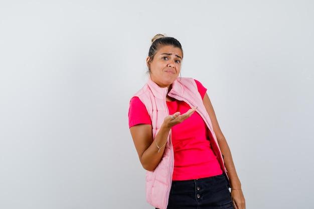 Kobieta w t-shircie, kamizelce pokazująca coś w pytającym stylu i wyglądająca na zdezorientowaną