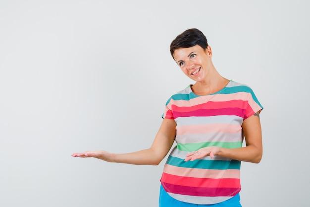 Kobieta w t-shircie w paski, pokazująca coś lub witająca i wyglądająca delikatnie
