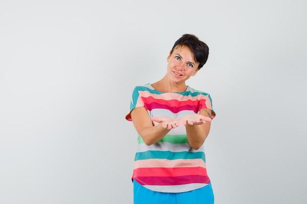 Kobieta w t-shircie w paski, spodnie coś oferującego i wyglądający delikatnie z przodu.