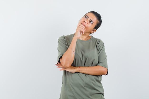 Kobieta w t-shirt, trzymając rękę na brodzie i niepewny patrząc