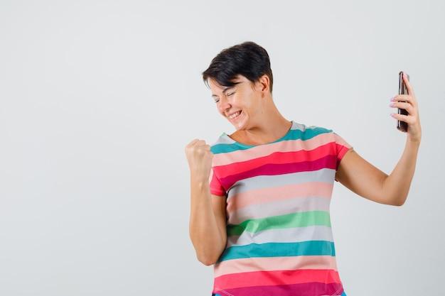Kobieta w t-shirt w paski pokazujący gest zwycięzcy, trzymając telefon komórkowy, widok z przodu.