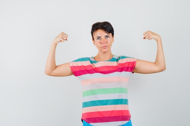Kobieta w t-shirt w paski pokazujący mięśnie ramion i wyglądający pewnie, widok z przodu.