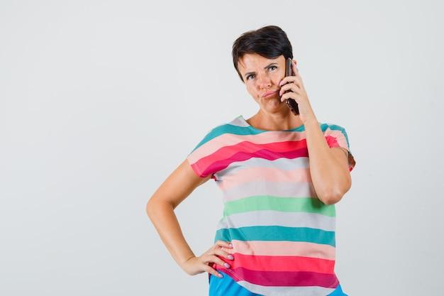 Kobieta w t-shirt w paski rozmawia przez telefon komórkowy i patrząc niepewny, widok z przodu.