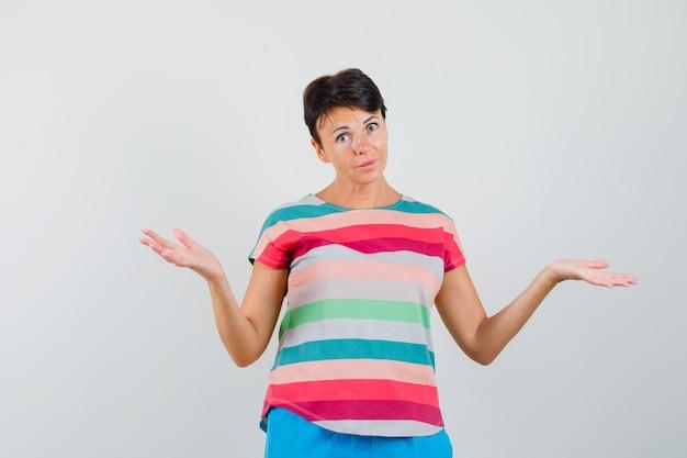 Kobieta w t-shirt w paski, spodnie robi gest wagi i wygląda na zdezorientowaną