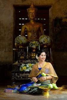Kobieta w tajlandzkiej sukience siedzi, aby złożyć kwiat lotosu i ofiarować mnichom w świątyni.