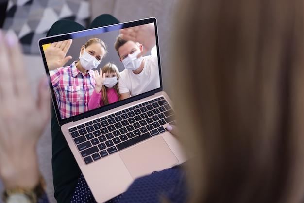 Kobieta w tle macha ręką do ekranu laptopa z wizerunkiem mężczyzny, kobiety i dziewczynki