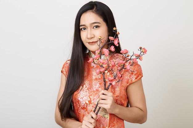 Kobieta w tradycyjny chiński czerwony strój śliwkowe kwiaty