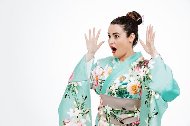 Kobieta w tradycyjnym japońskim kimonie patrząca na bok, szczęśliwa i podekscytowana, unosząca ręce w zdziwionym wyrazie na białym tle