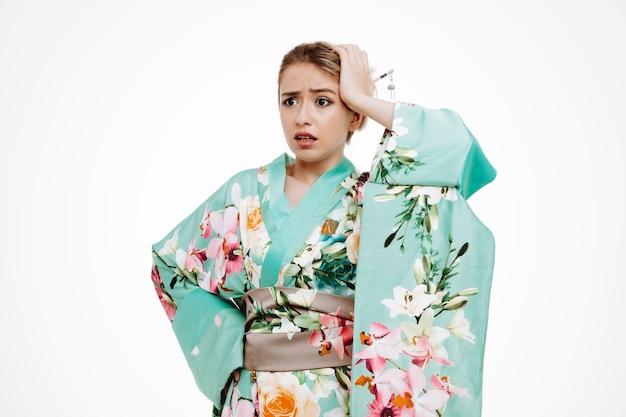 Kobieta w tradycyjnym japońskim kimonie patrząca na bok zdezorientowana i zmartwiona, trzymająca rękę na głowie za błąd na białym tle