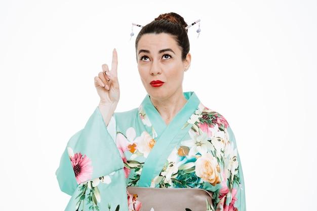 Kobieta w tradycyjnym japońskim kimonie patrząca w górę, wskazująca palcem wskazującym w górę, mająca wątpliwości, które są mylone na białym tle