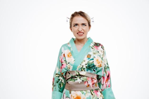 Kobieta w tradycyjnym japońskim kimonie patrzy zirytowana i zirytowana, robiąc krzywe usta na biało