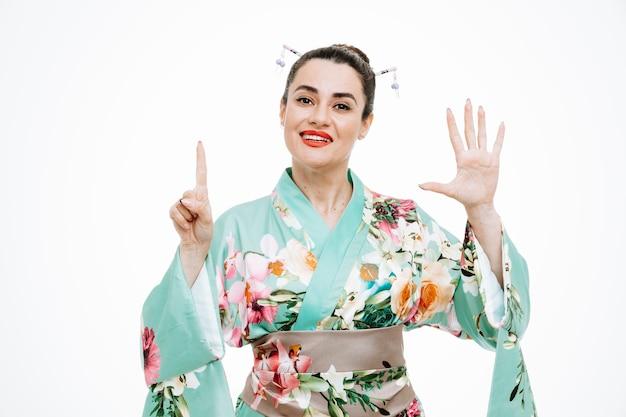 Kobieta w tradycyjnym japońskim kimonie szczęśliwa i pozytywna pokazująca numer sześć z palcami na białym