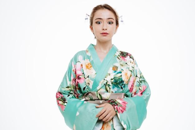 Kobieta w tradycyjnym japońskim kimonie szczęśliwa i pozytywna uśmiechnięta pewna siebie na białym