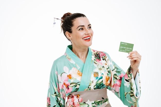 Kobieta w tradycyjnym japońskim kimonie trzymająca kartę kredytową, patrząca na bok, uśmiechnięta pewna siebie, szczęśliwa i pozytywna na białym tle