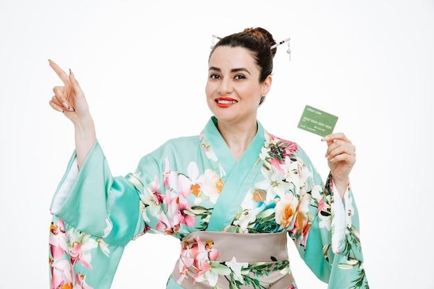 Kobieta w tradycyjnym japońskim kimonie trzymająca kartę kredytową wskazującą palcem wskazującym na bok na białym tle