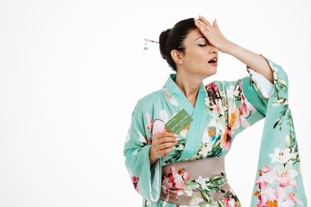 Kobieta w tradycyjnym japońskim kimonie trzymająca kartę kredytową wyglądająca na zdezorientowaną i rozczarowaną, trzymając rękę na głowie za błąd na białym tle