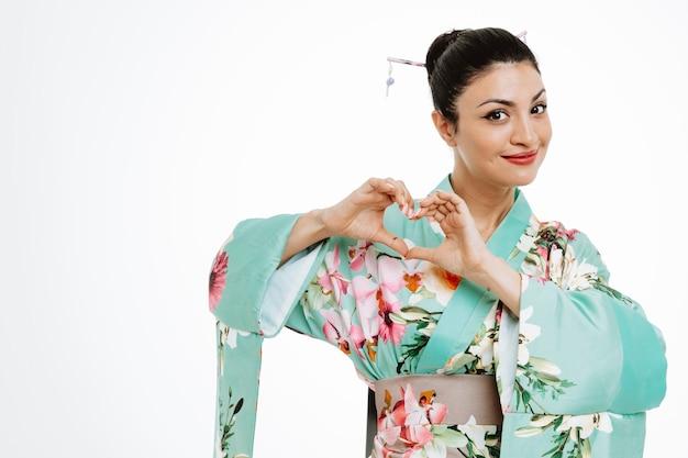 Kobieta w tradycyjnym japońskim kimonie uśmiecha się, robiąc gest serca palcami szczęśliwymi i pozytywnymi na białym