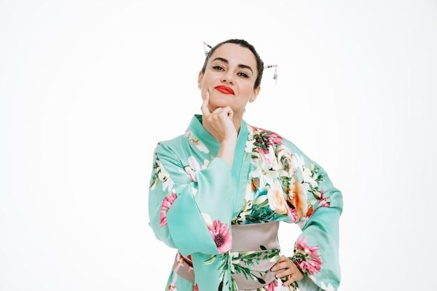 Kobieta w tradycyjnym japońskim kimonie z zamyślonym wyrazem twarzy, trzymająca rękę na brodzie, myśląca na biało