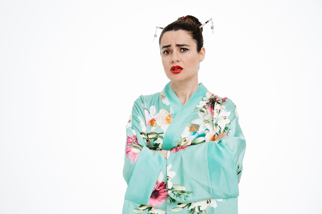 Kobieta w tradycyjnym japońskim kimonie ze sceptycznym wyrazem twarzy z rękami skrzyżowanymi na biało
