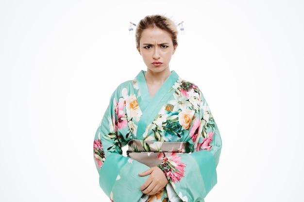 Kobieta w tradycyjnym japońskim kimonie ze zmarszczoną gniewną twarzą na białym tle