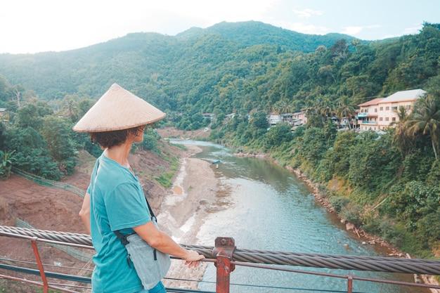 Kobieta w tradycyjnym kapeluszu patrząc na przestarzałą kładkę nad rzeką w wiosce muang khua w północnym laosie, cel podróży w azji południowo-wschodniej