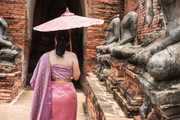 Kobieta w tradycyjnym tajskim różowym stroju w starożytnej świątyni i posąg buddy