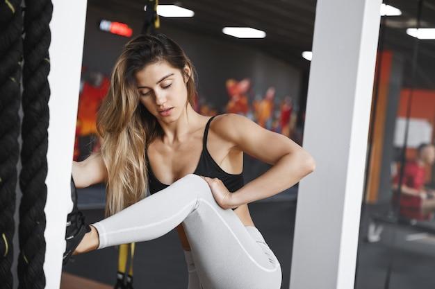 Kobieta w trakcie rozgrzewki na siłowni podnosi nogę na kolumnie rozciągającej się przed treningiem atletycznym.