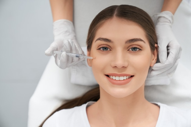 Kobieta w trakcie wykonywania zabiegu poprawy skóry twarzy