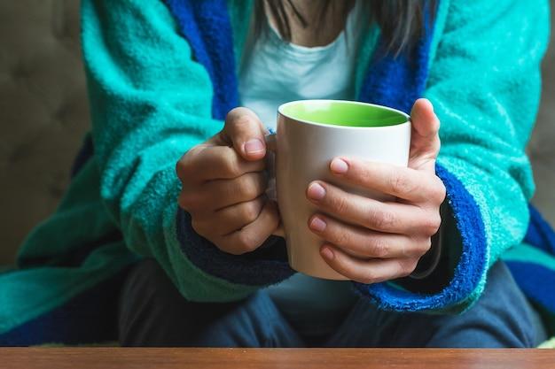 Kobieta w turkusowych szatach trzyma filiżankę herbaty