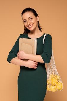 Kobieta w ubranie niosące torbę wielokrotnego użytku żółwia