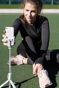 Kobieta w vlogger odzieży sportowej siedzi na zewnątrz sztucznej murawy
