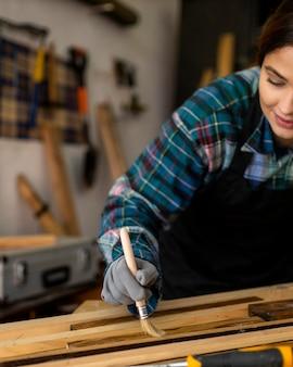 Kobieta w warsztacie szczotkująca kurz z desek drewnianych